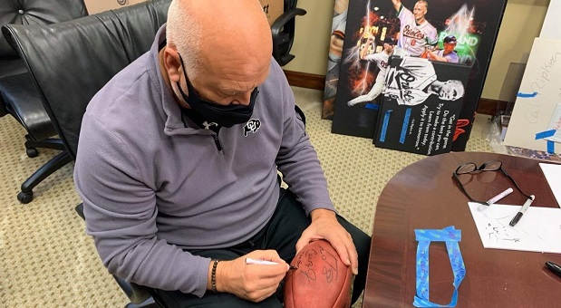 Orioles great Cal Ripken Jr. signs a football to be auctioned off to benefit the struggling Baltimore restaurant industry. (Submitted Photo)