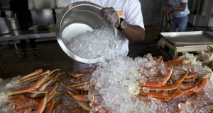 Antoine Saint-eyr covers jumbo crab legs with ice at Captain White's fresh seafood market at The Wharf along the Washington Cannel in Washington, Thursday, July 30, 2015. You could easily spend a whole visit to Washington exploring the museums, galleries and monuments along the National Mall. But that would be wrong. You'd miss out on all the energy, nightlife, parks, culture, sports and interesting food and drink in D.C.'s thriving neighborhoods. (AP Photo/Carolyn Kaster)