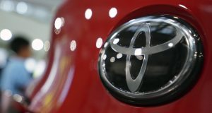FILE - In this Aug. 2, 2019, file, photo, people walk by the logo of Toyota at a show room in Tokyo. Toyota will pay $180 million to settle U.S. government allegations that it failed to report pollution control system defects in its vehicles for a decade. The company, on Thursday, Jan. 14, 2021,  also agreed in court to investigate future emissions-related defects quickly and report them to the U.S. Environmental Protection Agency in a timely manner.  (AP Photo/Eugene Hoshiko, File)
