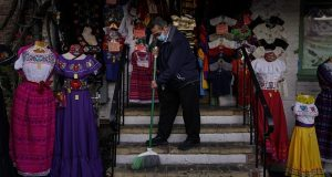 Victor Flores, 66, a third-generation owner of a gift shop, sweeps the steps of his store on Olvera Street in downtown Los Angeles, Wednesday, Dec. 16, 2020. Millions of business owners are about to get additional help as they weather the coronavirus outbreak. (AP Photo/Jae C. Hong, file)