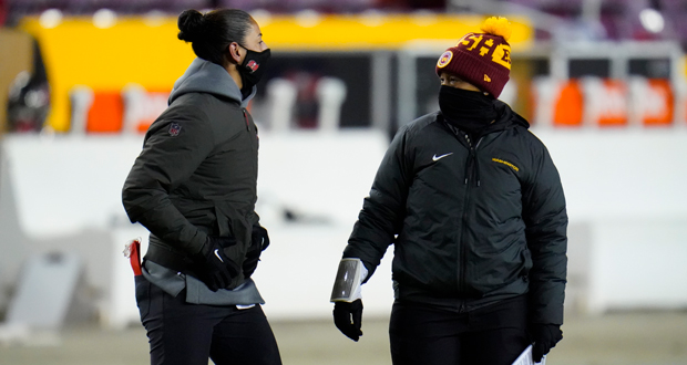 Tampa Bay Buccaneers assistant strength/conditioning coach Maral Javadifar, left, talking with Washington full-year coaching intern Jennifer King, right, following the conclusion of an NFL wild-card playoff football game, Saturday, Jan. 9, 2021, in Landover, Md. Tampa Bay won 31-23. (AP Photo/Julio Cortez)