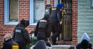 A Baltimore Police forensics team enters the house in West Baltimore where a U.S. Marshall was shot while while serving an arrest warrant on Thursday, Feb. 4, 2021. Baltimore police spokeswoman Lindsey Eldridge said in an email that the suspect was shot by return fire and died after Thursday morning's shooting. (Jerry Jackson/The Baltimore Sun via AP)