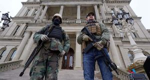 FILE - In this Jan. 6, 2021, file photo, armed men stand on the steps at the State Capitol after a rally in support of President Donald Trump in Lansing, Mich. In the past year, insurrectionists have breached the U.S. Capitol and protesters have forced their way into statehouses around the country. But the question of whether guns should be allowed in capitol buildings remains political and states are going in opposite directions. (AP Photo/Paul Sancya, File)