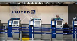 FILE - In this Oct. 14, 2020 file photo, United Airlines employees work at ticket counters in Terminal 1 at O'Hare International Airport in Chicago.  United Airlines will pay more than $49 million to settle criminal and civil accusations of defrauding the post office in the handling of international mail. The Justice Department said Friday, Oct. 26, 2021, that former employees of United's cargo division falsified parcel delivery information for several years.  (AP Photo/Nam Y. Huh, File)