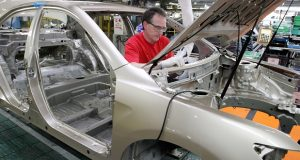 FILE - In this Feb. 25, 2010 file photo, production team member Darryl Ashley installs an inner dash silencer in a Camry on the assembly line at the Toyota Motor Manufacturing plant in Georgetown, Ky. For the first time in more than 20 years, U.S. automakers are questioning a pillar of manufacturing: The practice of bringing parts to assembly lines right before they're used. The March 2011 earthquake knocked out many Japanese parts makers, resulting in factory shutdowns, including this one for a few days, and model shortages around the world. (AP Photo/James Crisp)