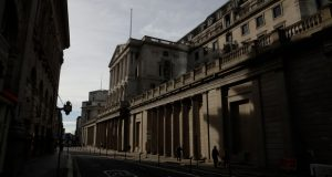 People walk past the Bank of England in the City of London financial district of London, during England's third coronavirus lockdown, Tuesday, Feb. 23, 2021. British Prime Minister Boris Johnson announced on Monday a slow easing of one of Europe's strictest pandemic lockdowns, with non-essential shops and hairdressers due to reopen April 12. (AP Photo/Matt Dunham)