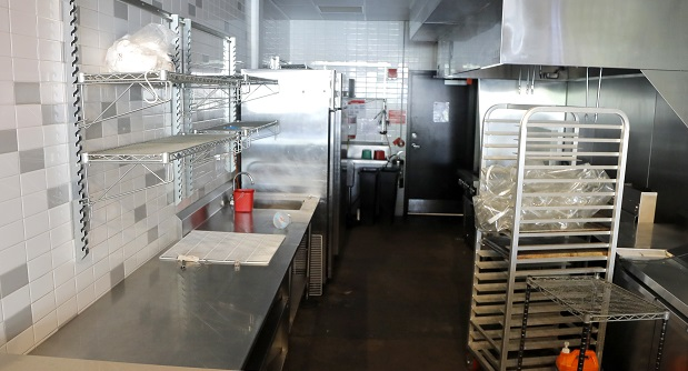 A stall reserved for pop-up restaurants at Baltimore's R. House food hall sits empty in July. The city Wednesday announced some loosening of dining restrictions. (AP File Photo/Julio Cortez)