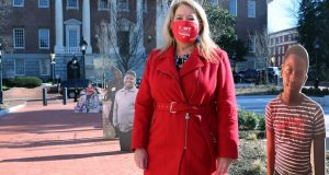 Cheryl Bost, president of the Maryland State Education Association, stands outside the Maryland State House in Annapolis, Md., on Monday, Feb. 8, 2021, with cardboard cutouts of students before the House of Delegates voted to override Gov. Larry Hogan's veto of a comprehensive K-12 education measure that will steer billions in new funding to schools over the next decade. The Maryland Senate will still need to override the veto for the measure to become law. (AP Photo/Brian Witte)