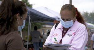 """A """"promotora"""" (health promoter) from CASA, a Hispanic advocacy group, tries to enroll Latinos as volunteers to test a potential COVID-19 vaccine, at a farmers market in Takoma Park, Maryland on Sept. 9, 2020. Minority enrollment in studies of two shots has inched up in recent weeks, but even more is needed this fall as additional vaccine testing gets underway over the next two months. (AP Photo/Federica Narancio)"""