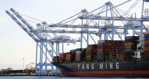 FILE - In this Nov. 4, 2019, file photo, cargo cranes are used to take containers off of a Yang Ming Marine Transport Corporation boat at the Port of Tacoma in Tacoma, Wash.  The Commerce Department said Thursday, Jan. 7, 2021, the U.S. trade deficit jumped to $68.1 billion in November as a surge in imports overwhelmed a smaller increase in exports. (AP Photo/Ted S. Warren, File)