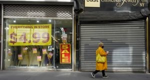 A pedestrian walks past a shuttered store and one that is having a store closing sale in New York's Financial District, Tuesday, March 23, 2021.  The U.S. economy grew at an annual rate of 4.3% in the final three months of 2020, slightly faster than previously estimated, as recovery expectations for 2021 rise along with vaccinations as the U.S.  unleashes nearly $2 trillion in government support. (AP Photo/Mary Altaffer)