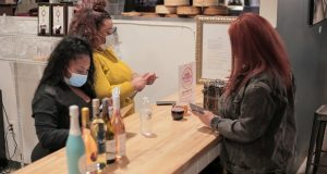 Ashley Payne-El, left, and Virginia Wilkens, the owners of Wine O'Clock, help a customer at their stall at the Mount Vernon Marketplace. (Submitted Photo)