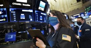FILE - In this Wednesday Trader Phyllis Arena Woods works on the New York Stock Exchange trading floor on March 10. A year earlier, a free fall for the stock market suddenly ended, ushering in one of its greatest runs. (Nicole Pereira/New York Stock Exchange via AP)