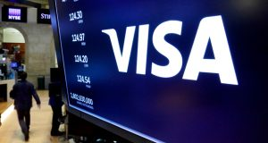 FILE- In this April 23, 2018, file photo, the logo for Visa appears above a trading post on the floor of the New York Stock Exchange.  Visa is under investigation by the Department of Justice's antitrust division over whether the company pushes merchants into more expensive forms of debit card payments, The Wall Street Journal reported Friday, March 19, 2021. The investigation is focused on how merchants route debit card transactions when a consumer makes an online transaction, according to the Journal, which cited anonymous sources.(AP Photo/Richard Drew, File)