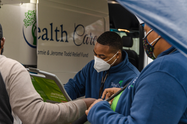 Brandon Brown, a Total Health Care Mobile Health Unit driver and outreach specialist, checks in a patient. (Photo by Justin Jacobs, Glasshouse Media & Production)