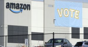 FILE - In this March 30, 2021 file photo, a banner encouraging workers to vote in labor balloting is shown at an Amazon warehouse in Bessemer, Ala.  The retail union that failed to unionize Amazon workers at the Alabama warehouse wants the results to be thrown out, saying that the company illegally interfered with the voting process.The Retail, Wholesale and Department Store Union said in a filing that Amazon threatened workers with layoffs and even the closing of the warehouse if they unionized. (AP Photo/Jay Reeves, File)