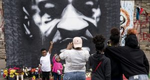 A family takes an image in front of a mural of the deceased George Floyd as demonstrators gather for a solidarity rally in memory of Floyd and Daunte Wright outside Cup Foods, Sunday, April 18, 2021, in Minneapolis. (AP Photo/John Minchillo)