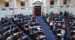 Members of the Maryland House of Delegates sit socially distanced on the last day of the state's 90-day legislative session on Monday, April 12, 2021 in Annapolis, Md. Other members of the 141-member body have been participating via video from a nearby annex to avoid having too many people in the chamber as a precaution during the pandemic. (AP Photo/Brian Witte)