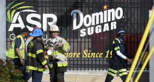 Firefighters and workers stand near the entrance to a Domino Sugar plant where a fire broke out, Tuesday, April 20, 2021, in Baltimore. (AP Photo/Steve Ruark)