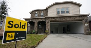 A sold sign stand in front of new home under construction Monday, March 15, 2021, in Houston.  Sales of new homes surged 20.7% in March, rebounding from a drop in February caused in part by severe winter storms in many parts of the country.  (AP Photo/David J. Phillip)