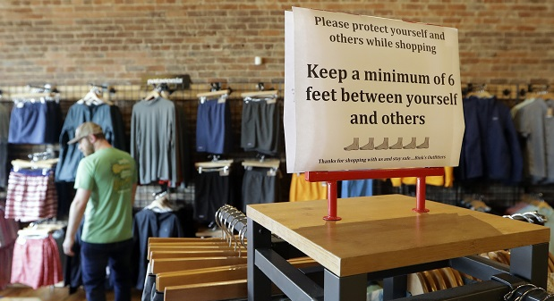 A sign reminding shoppers of the need for social distancing, a ubiquitous sight in retail shops during the pandemic. (AP File Photo/Mark Humphrey)