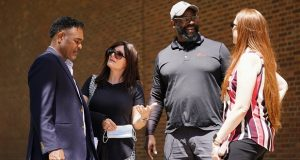 From left, former NFL player Ken Jenkins and his wife Amy Lewis, along with former NFL player Clarence Vaughn III and his wife Brooke Vaughn, meet before delivering tens of thousands of petitions demanding equal treatment for everyone involved in the settlement of concussion claims against the NFL, to the federal courthouse in Philadelphia, Friday, May 14, 2021. (AP Photo/Matt Rourke)