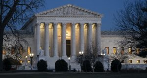 Night falls on the Supreme Court in Washington. The Supreme Court is considering whether to hear the case of a Black man who says he suffered discrimination because the N-word was carved into the wall of the hospital elevator where he worked. (AP Photo/J. Scott Applewhite, File)