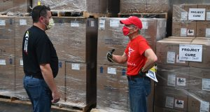 Jason Fraker, left, manager of the University of Maryland Medical System warehouse, and Project C.U.R.E. volunteer driver Larry Colletta have a conversation in front of pallets of COVID supplies in the warehouse (Photo Courtesy of University of Maryland Medical Syatem)