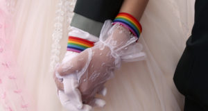 Lesbian couples Chen Ying-hsuan, right, holds Li Li-chen's hand during a military mass weddings ceremony in Taoyuan city, northern Taiwan, Friday, Oct. 30, 2020. (AP Photo/Chiang Ying-ying)