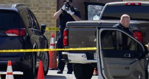 Shattered glass is seen on a pickup's driver side door as investigators document the scene in a mall parking area where two Baltimore city police officers were shot and a suspect was killed as a U.S. Marshals' task force served a warrant, Tuesday, July 13, 2021, in Baltimore. (AP Photo/Julio Cortez)