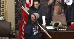 In this file image from U.S. Capitol Police video, Paul Allard Hodgkins, 38, of Tampa, Fla., front, stands in the well on the floor of the U.S. Senate on Jan. 6, 2021, at the Capitol in Washington. (U.S. Capitol Police via AP, File)
