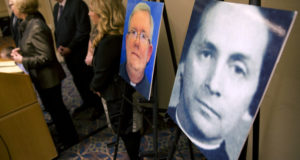 In this Nov. 13, 2013, file photo, a photo of the Rev. Robert Brennan, right, is displayed during a news conference in Philadelphia. Federal prosecutors in Philadelphia charged Brennan, a former Roman Catholic priest with lying to the FBI about whether he knew the accuser and his family. (AP Photo/Matt Rourke, File)