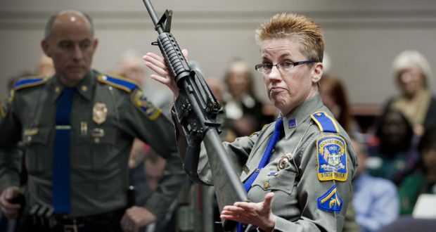 In this Jan. 28, 2013, file photo, firearms training unit Detective Barbara J. Mattson, of the Connecticut State Police, holds up a Bushmaster AR-15 rifle, the same make and model of gun used by Adam Lanza in the Sandy Hook School shooting, for a demonstration during a hearing of a legislative subcommittee reviewing gun laws, at the Legislative Office Building in Hartford, Conn. (AP Photo/Jessica Hill, File)