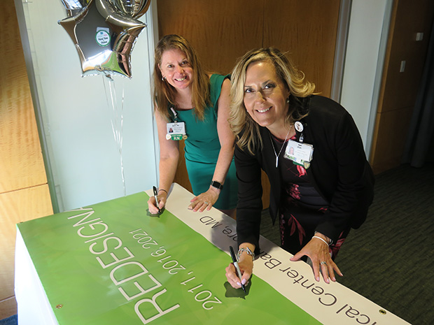 Kim Schwenk MSN, RN, left, Mercy's vice president and chief nursing officer and Beth Kilmoyer DNP, RN-BC, Mercy's magnet program director, sign the Magnet recognition banner. (Photo courtesy of Mercy Medical Center)