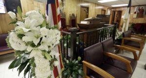 A memorial wreath stands near the pulpit in the basement at Mother Emanuel AME Church in Charleston, S.C., on June 17, 2016, one year after nine black parishioners were killed during Bible study. (AP Photo/Chuck Burton)