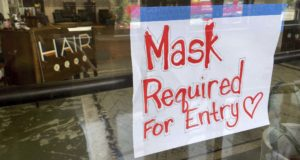 This July 28, 2021, file photo shows a sign on the door of a hair salon informing patrons that masks are required to be in the business in Kansas City, Mo. Businesses large and small are reinstituting mask mandates and requiring vaccines of their customers as U.S. coronavirus cases rise. (Jill Toyoshiba/The Kansas City Star via AP, File)