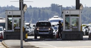 A Canada Border Services Agency officer hands documents back to a motorist entering Canada at the Douglas-Peace Arch border crossing, in Surrey, British Columbia, Canada, on Aug. 9 2021. The U.S. government on Friday, Aug 20, extended a ban on nonessential travel along the borders with Canada and Mexico to slow the spread of COVID despite increase pressure to lift the restriction. (Darryl Dyck/The Canadian Press via AP, File)