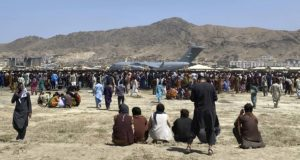 Hundreds of people gather on Aug. 16, 2021, near a U.S. Air Force C-17 transport plane at the perimeter of the international airport in Kabul, Afghanistan. (AP Photo/Shekib Rahmani)