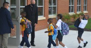 Youngsters enter the first new Catholic school built in Baltimore in roughly 60 years with a mix of enthusiasm and first-day-back jitters Aug. 30, 2021. The new 65,000-square-foot school near downtown Baltimore is an anomaly in the national education landscape where the pandemic has shuttered many parish schools. (AP Photo/David McFadden)