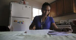 Mary Taboniar, a housekeeper at the Hilton Hawaiian Village resort in Honolulu, looks over bills at her home in Waipahu, Hawaii, on Sept. 4, 2021. Taboniar went 15 months without a paycheck, thanks to the COVID-19 pandemic. The single mother of two saw her income completely vanish as the virus devastated the hospitality industry. (AP Photo/Caleb Jones)
