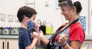 In this Aug. 12, 2021, file photo, a student gets help with his mask from transitional kindergarten teacher Annette Cuccarese during the first day of classes at Tustin Ranch Elementary School in Tustin, California. Now that California schools have welcomed students back to in-person learning, they face a new challenge: A shortage of teachers and all other staff, the likes of which some districts say they've never seen. (Paul Bersebach/The Orange County Register via AP, File)