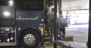 In this Thursday, Feb. 13, 2020 file photo, agents for Customs and Border Protection board a Greyhound bus headed for Portland, Ore., at the Spokane Intermodal Center, a terminal for buses and Amtrak, in Spokane, Wash. Greyhound Lines Inc. will pay $2.2 million to settle a lawsuit over the bus line's practice of allowing U.S. Customs & Border Protection agents to board its buses in Washington state to conduct warrantless immigration sweeps, the state attorney general said Monday, Sept. 27, 2021. (AP Photo/Nicholas K. Geranios, File)