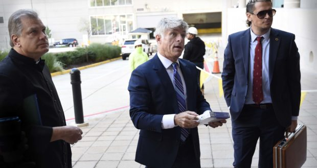 Fr. Paul Kalchik, left,St. Michael's founder and CEO Michael Voris, center, and Milo Yiannopoulos talk with a court officer before entering the federal courthouse, Sept. 30, 2021, in Baltimore. St. Michael's claims city officials cancelled the Nov. 16 rally because they disapprove of the group's religious message. (AP Photo/Gail Burton)