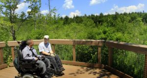 In this June 16 2011, photo, Chelsea Fernandes, left, and Mark Race take a break from hiking through the woods at the Crotched Mountain Rehabilitation Center in Greenfield, N.H. The center offers over 2.5 miles of privately funded trails designed to be easily accessible for people in wheelchairs and those who have difficulty walking. (AP Photo/Jim Cole)