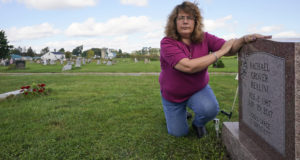 Sharon Grover rests her hands on the gravestone for her daughter, Rachael, on Sept. 28, 2021, at Fairview Cemetery in Mesopotamia, Ohio. Grover believes her daughter started using prescription painkillers around 2013 but missed any signs of her addiction as her daughter, the oldest of five children, remained distanced. (AP Photo/Tony Dejak)